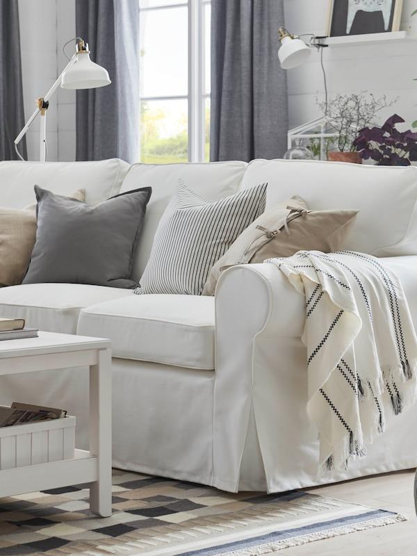 Valoisa olohuone, jossa on valkoinen EKTORP-sohva. Sohvalla on koristetyynyjä kuten harmaa GURLI, raidallinen INGALILL ja beige AINA. Sohvan käsinojalla on STINAMAJ-huopa.