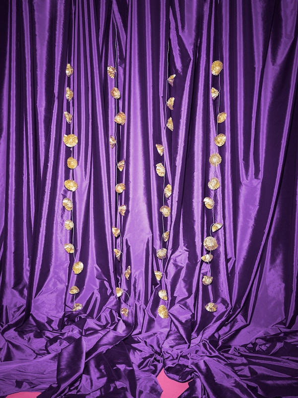 Guldfärgade KARISMATISK ljusslingor i blomformer hänger mot en bakgrund med lila satintyg.
