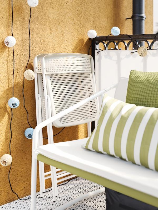 Deux chaises pliantes blanches/beiges contre un mur jaune, à côté d'une petite causeuse d'extérieur blanche décorée de deux coussins verts.