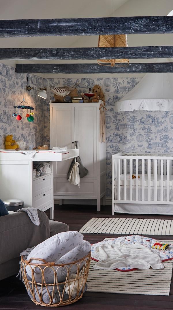 Pilha de têxteis numa caixa de madeira num quarto de criança, incluindo uma capa de edredão e fronha GULSPARV e cortinados GULSPARV.