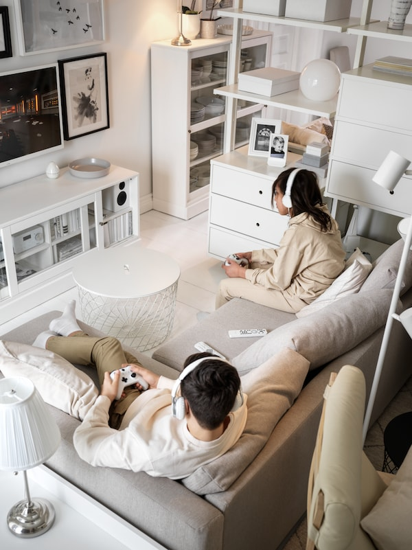 A living room in shades of white, with two teens in a beige FRIHETEN corner sofa-bed playing a video game, consoles in hand.
