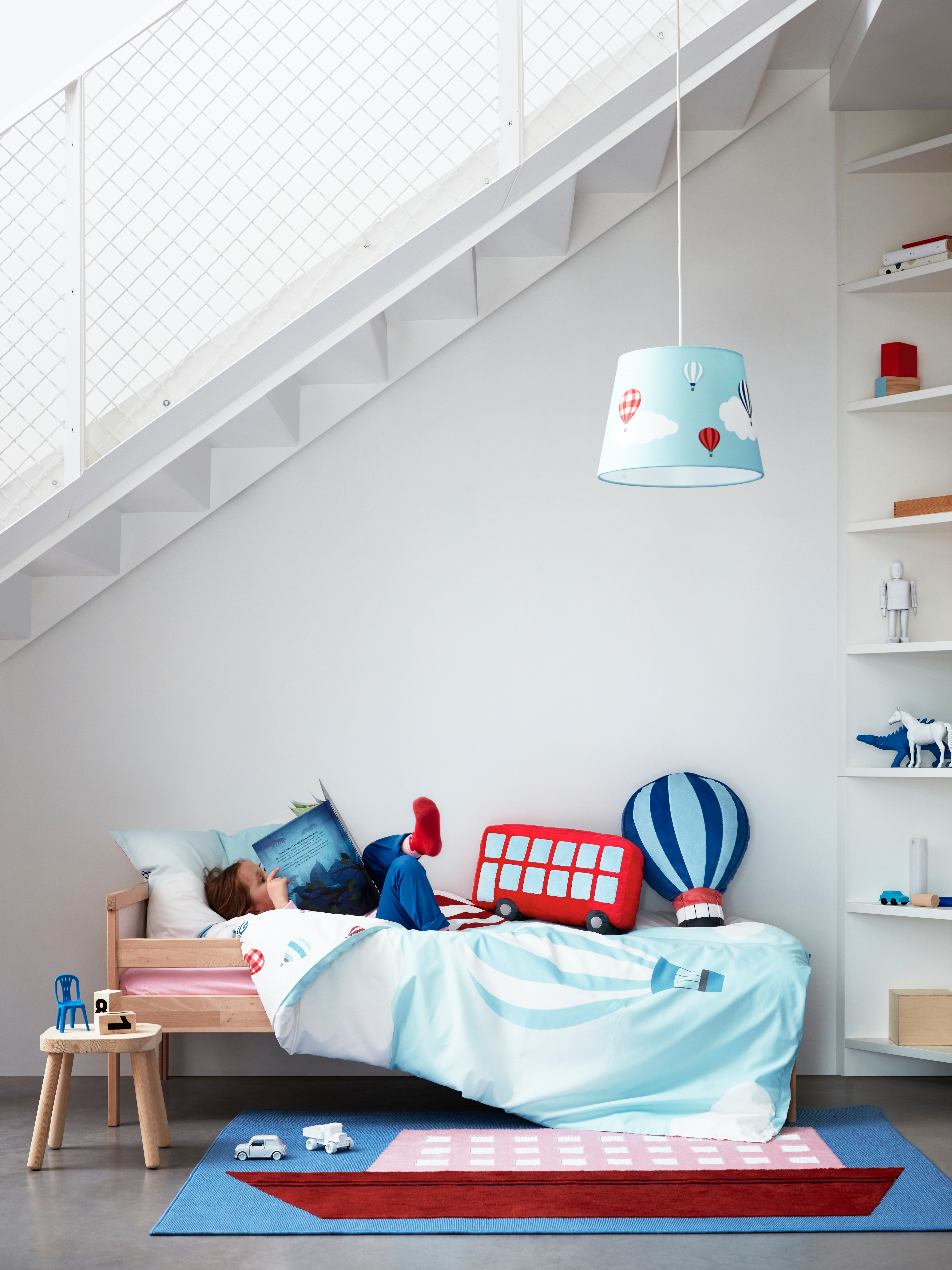 A kid lying reading on a bed with a blue UPPTÅG quilt cover with pillowcases in an air balloon pattern, toys on the bed.