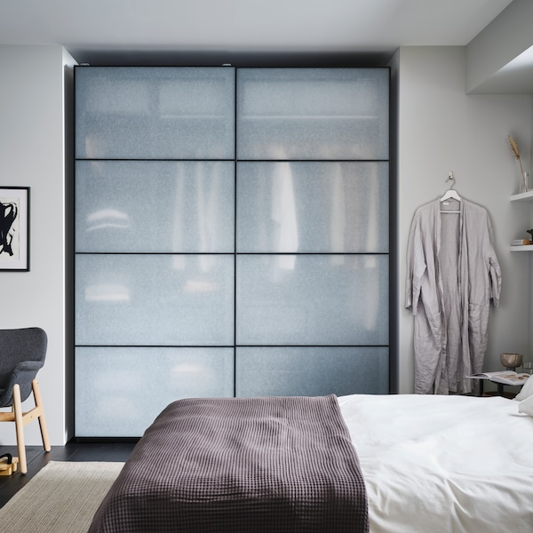 A PAX wardrobe with SVARTISDAL sliding doors in frosted glass stands in front of a bed.