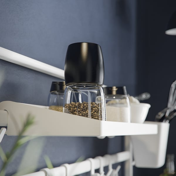 A white SUNNERSTA shelf with a salt and pepper shaker standing on top of it and with a rail with hooks below.