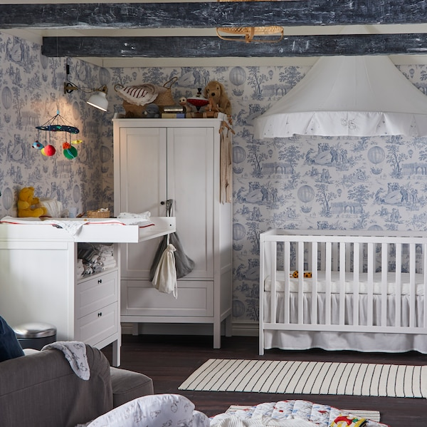 A white SUNDVIK cot, wardrobe and changing table stand in a traditional-style children's room with patterned wallpaper.