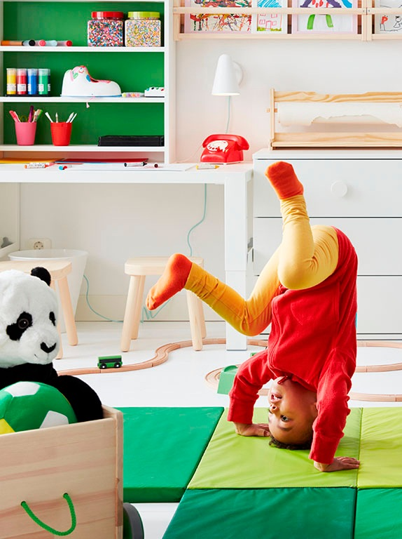 A child doing a headstand on a green PLUFSIG gym mat in front of a white GODISHUS chest of drawers and FLISAT stool.