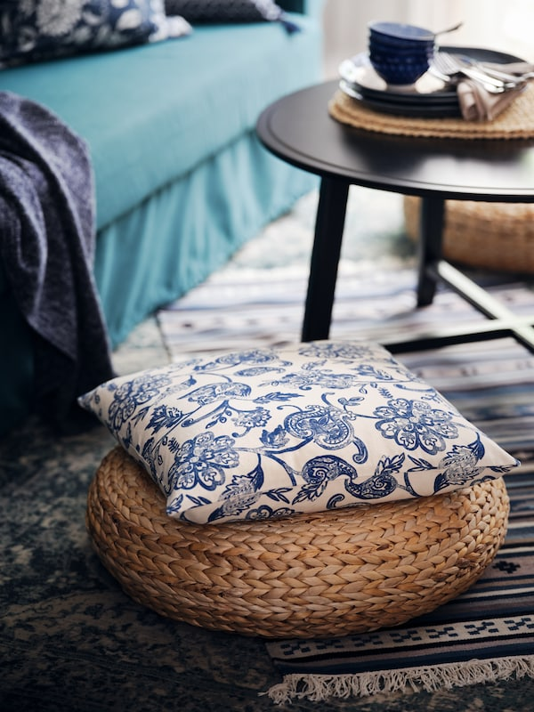 A cushion with a JUNIMAGNOLIA cover resting on an ALSEDA banana-fibre stool placed next to a black KRAGSTA coffee table.