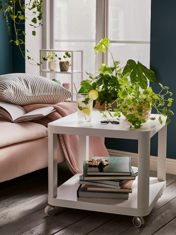 Ein würfelförmiger Beistelltisch mit Rollen und zwei Ablageflächen steht neben einer Récamiere. Auf der unteren Ablage liegen Bücher und auf der Tischplatte stehen Pflanzen und ein Glas.