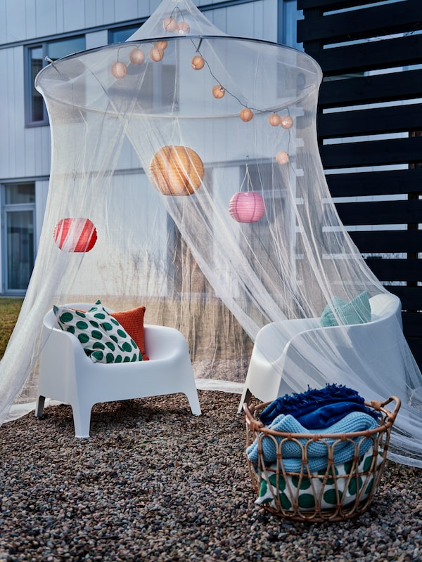 Courtyard setting with a decorated SOLIG net draped over plastic armchairs. A SNIDAD basket of textiles on the ground.