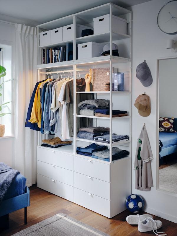 Hvid garderobeløsning med åben og lukket opbevaring, integreret belysning, skjorter på bøjler, bukser, der er lagt sammen, kasketter og hvide kasser.