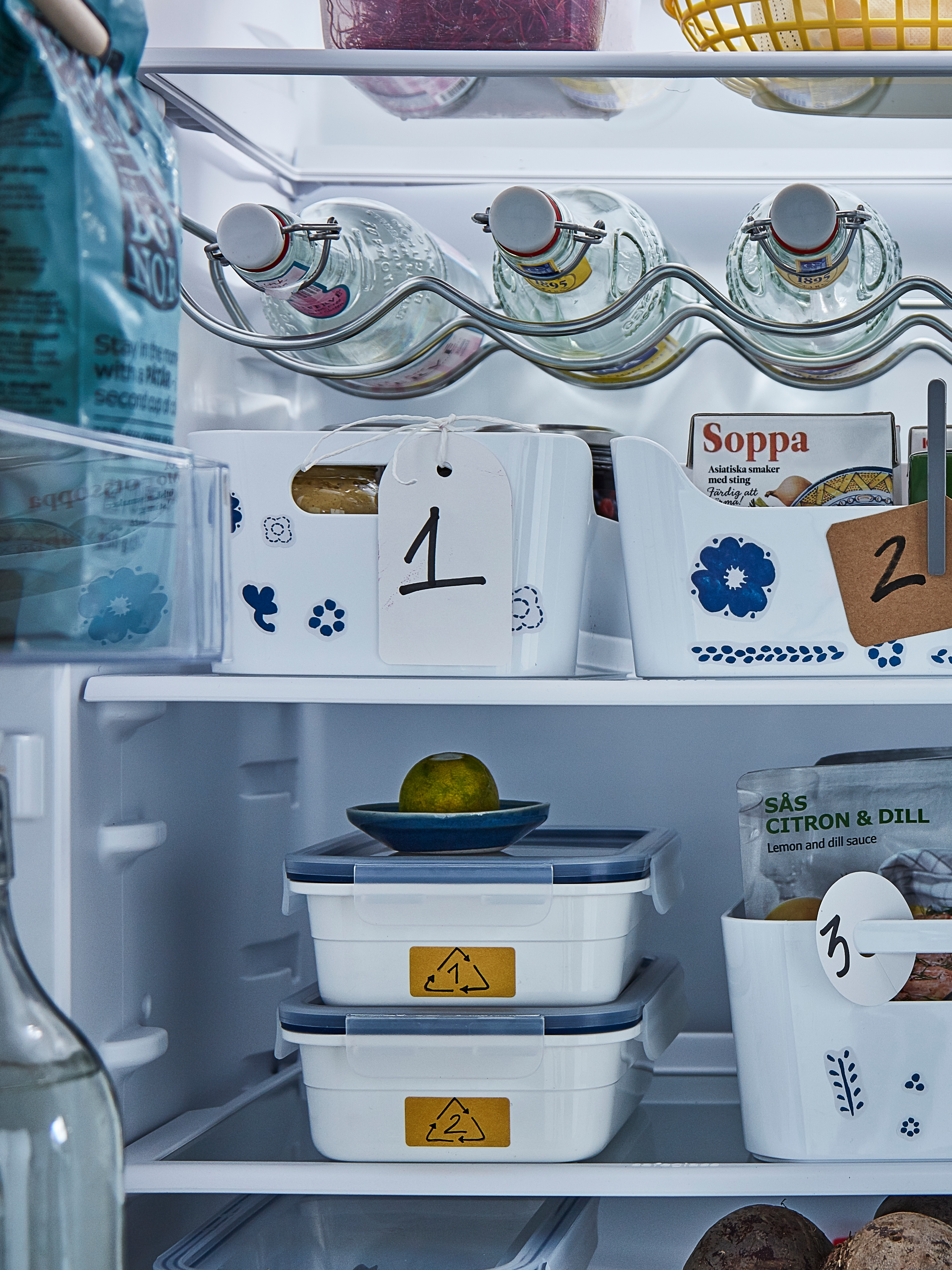 White VARIERA boxes in a refrigerator filled with groceries and lunch boxes, stacked on each other.