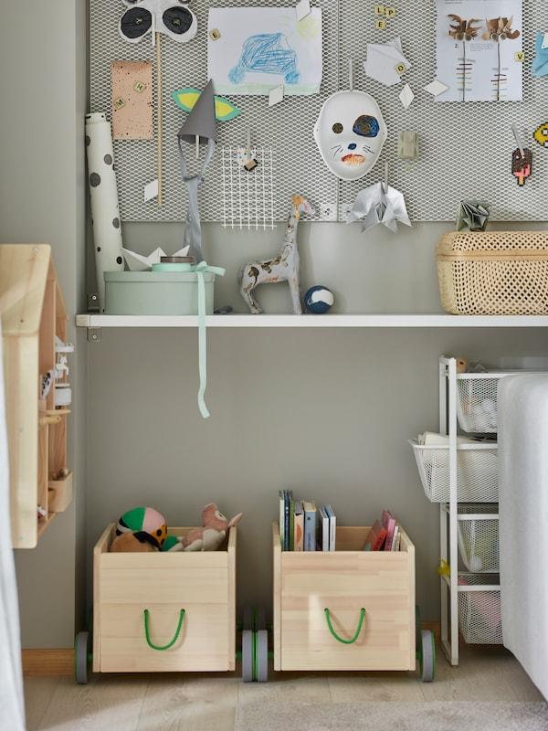 Două unități de depozitare pentru jucării FLISAT din lemn masiv de pin, cu roți gri și mânere verzi, depozitează cărți pentru copii și multe altele.