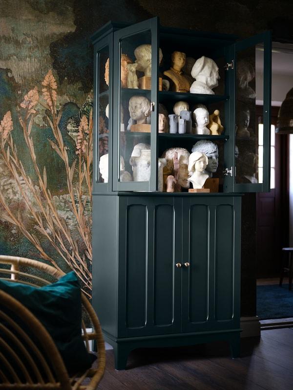 Um armário com portas de vidro LOMMARP, em azul esverdeado escuro, apresentando muitas cabeças e bustos em cerâmica, encostado a uma parede.