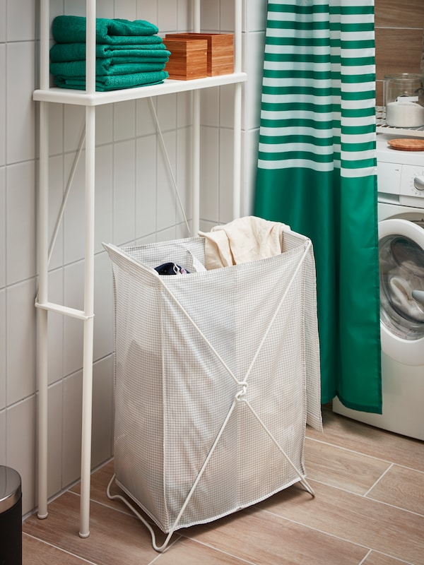 TORKIS laundry baskets by a washing machine with a green shower curtain.