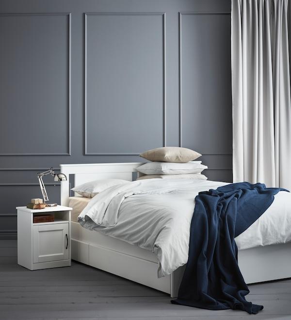 Łóżko SONGESAND w szarym pokoju.