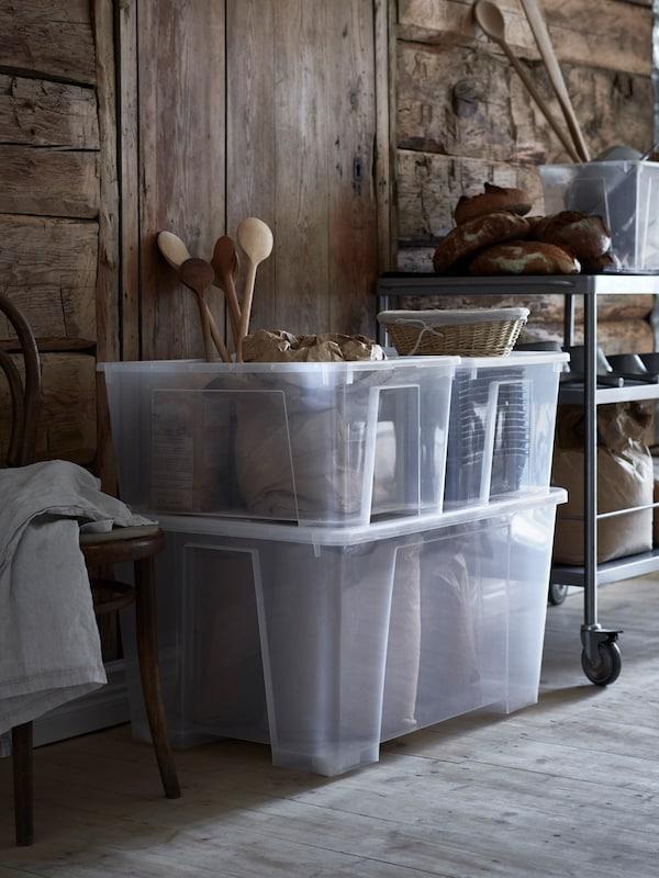 Cajas SAMLA apiladas, con utensilios de cocina de madera en su interior, en un espacio rústico junto a un carrito metálico con pan y otros artículos.