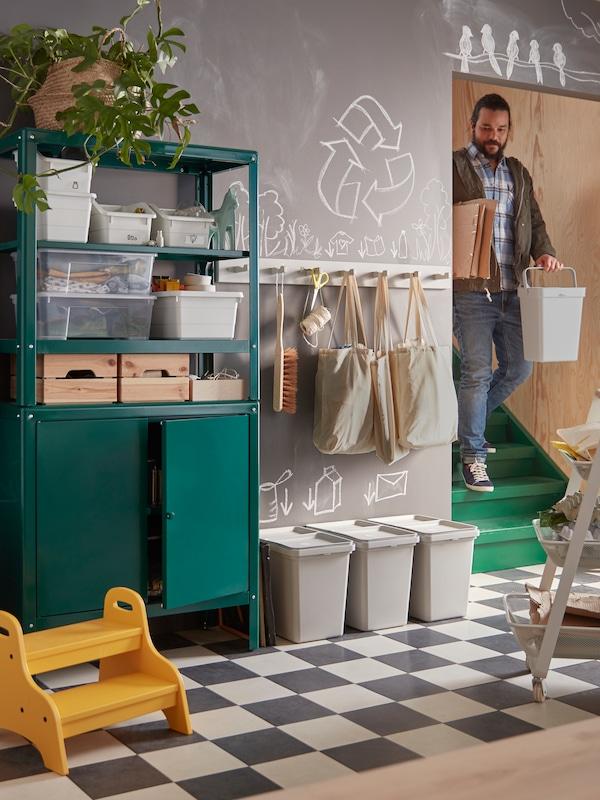 Ein Mann trägt Pappe und einen HÅLLBAR Behälter in den Keller, wo ein KOLBJÖRN Regal und weitere Behälter stehen.