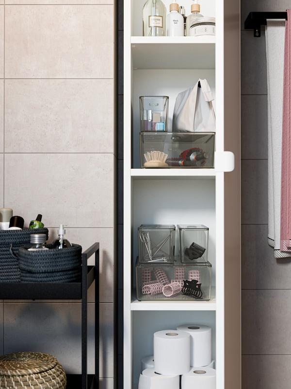 Un armario alto aberto en cor branca con caixas transparentes, papel hixiénico, cremas o moitas máis cousas no seu interior. Un carriño negro ao seu carón.