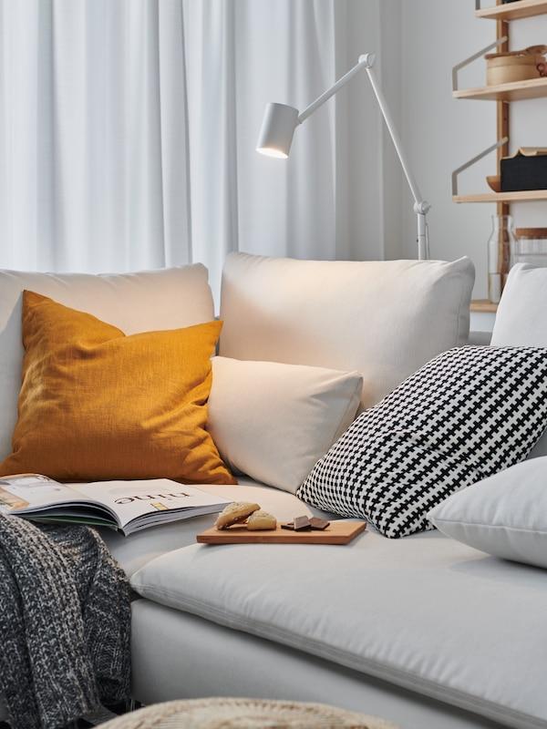A NYMÅNE floor/reading lamp illuminates the corner of a SÖDERHAMN sofa, made cosier with extra cushions and snacks.