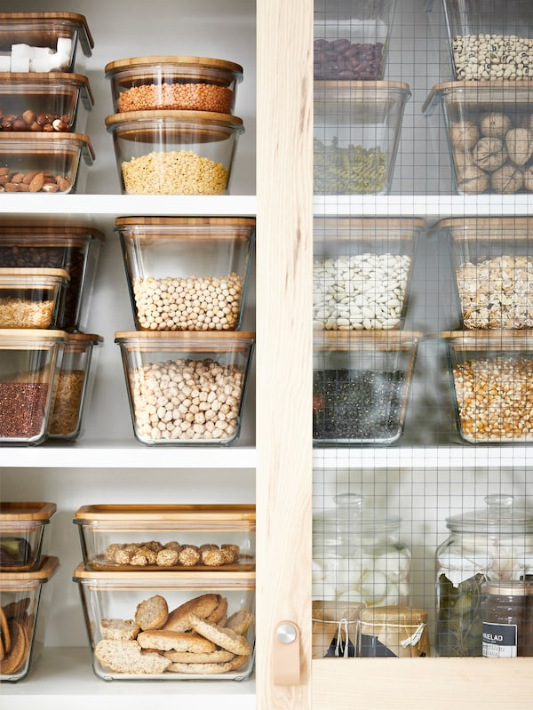 The inside of a neat kitchen cabinet filled with various food containers with dry goods inside.