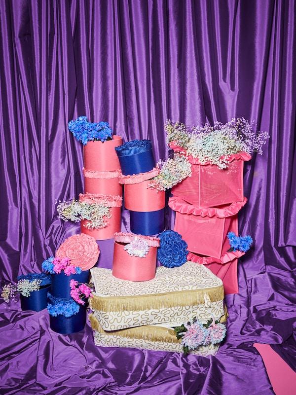Rosafarbene und blaue KARISMATISK Schachteln und Fächer und goldfarbene Taschen sind übereinandergestapelt; sie sind mit Blumen verziert.
