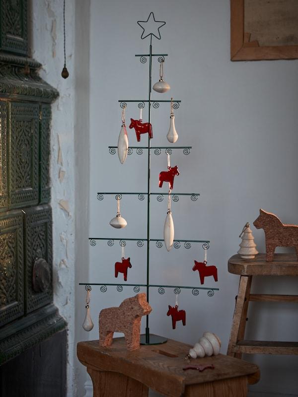 VINTER 2021 trä- och glasdekorationer hänger med klämmor på ett julgransformat prydnadsställ i metall med en stjärna högst upp.