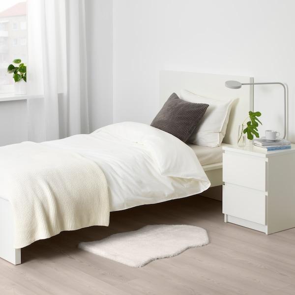 Valkoisessa makuuhuoneessa on TOFTLUND-matto, joka on aseteltu lattialle MALM-sängyn sekä MALM-yöpöydän viereen.