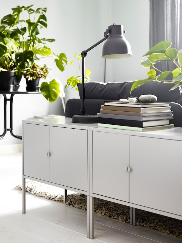 Dois armários de metal LIXHULT em cinzento, com livros e um candeeiro de secretária HEKTAR, ao lado de um sofá numa sala.