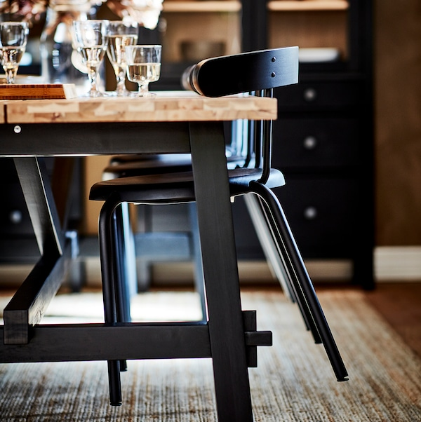 Chairs hanging on the edge of a table, as if for cleaning the floor, with glasses and other items on the table.