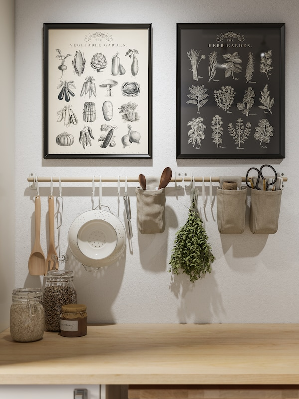 Kitchen accessories hanging from a white wall featuring 2 framed pictures.