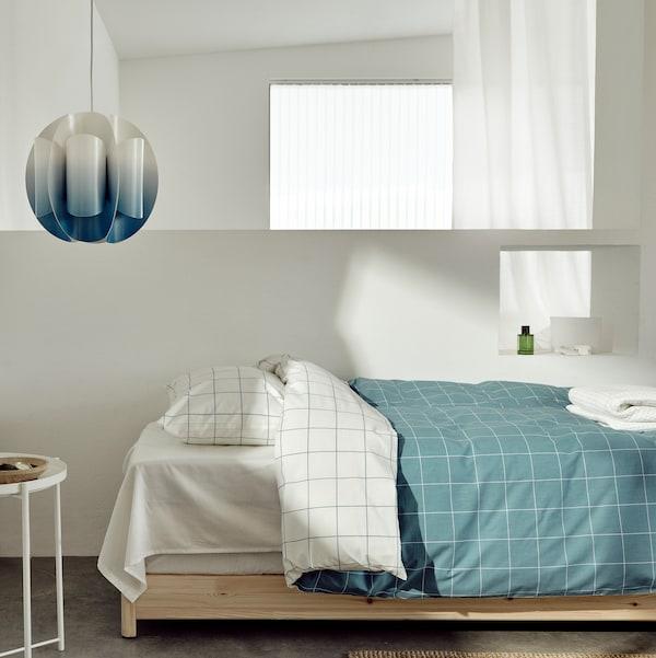 Voici une chambre à coucher avec une housse de couette VITKLÖVER et un abat-jour TRUBBNATE.