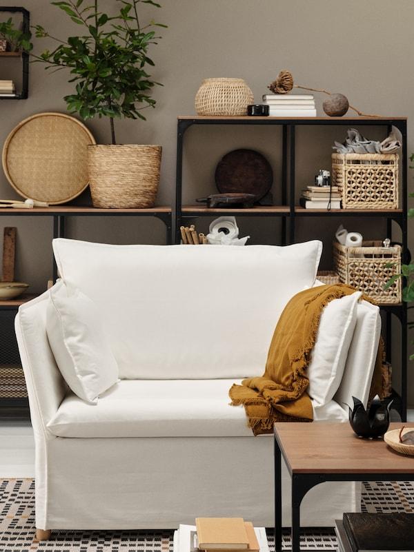 Kerusi berlengan 1.5 tempat duduk berwarna putih, alas berwarna coklat keemasan gelap, unit rak berwarna hitam dengan bakul, buku dan objek-objek lain.