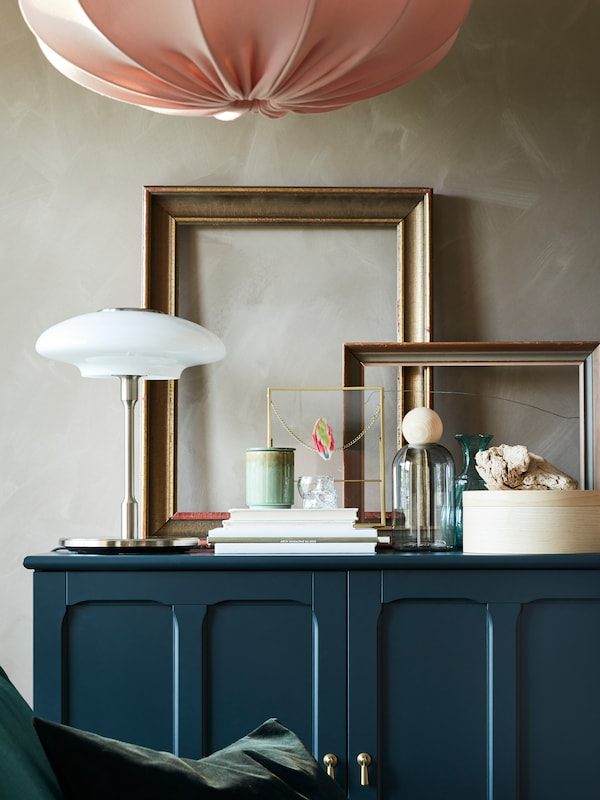 A blue storage unit with a lamp, some picture frames and diverse items placed on it, and a hanging lamp.