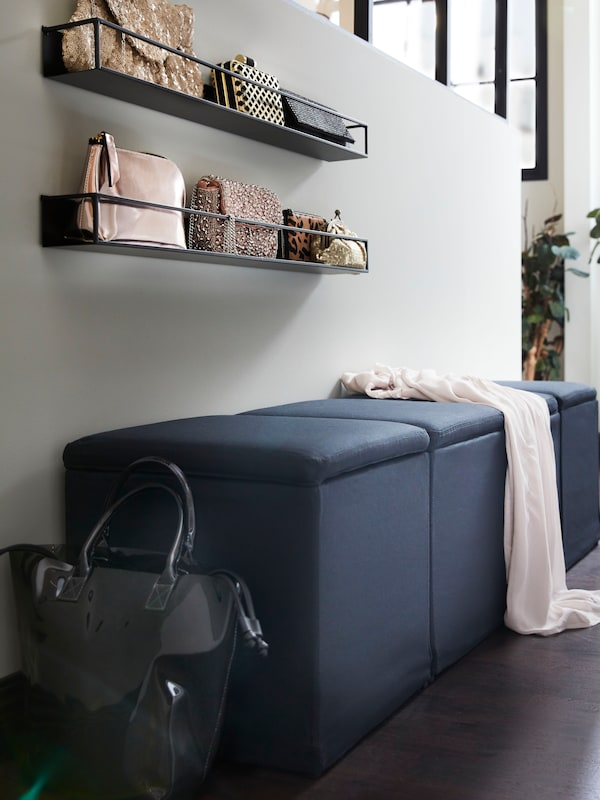 Three black storage boxes are lined up against a wall. A collection of evening bags sits above them on open shelving.
