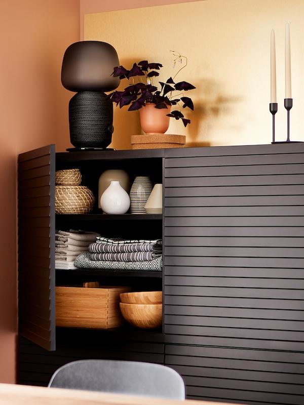 Et svart BESTÅ/STOCKVIKEN skap med ei dør åpen, med bordduker, vaser og boller inni og ei høyttalerlampe på toppen.