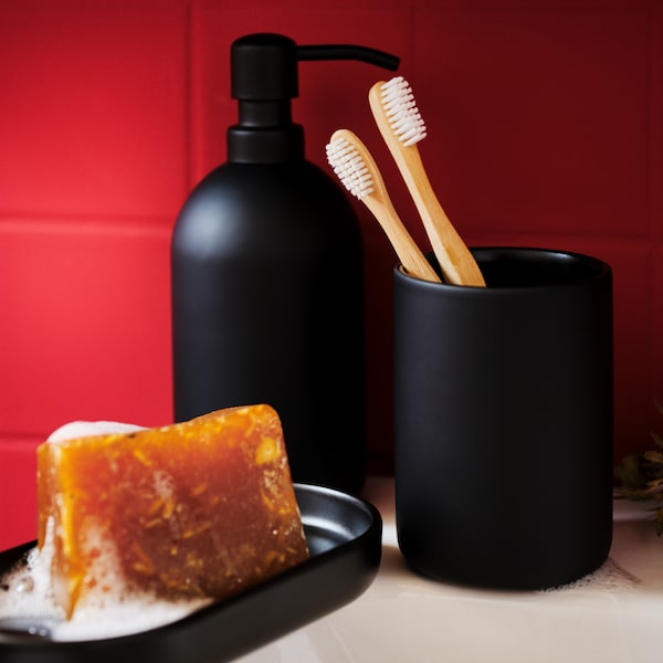 A dark-matte, stoneware GANSJÖN three-piece bathroom set on the side of a white washbasin, next to a red-tiled wall.