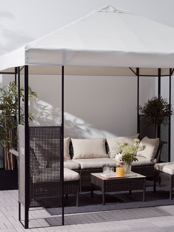 A gazebo with a white roof and dark brown frame, an outdoor sofa and chairs with cushions, and a table with plants.