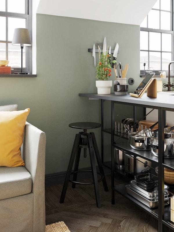 Černá barová stolička vedle otevřených polic se šedou pracovní deskou s nádobím, nahoře je stojan na tablety a květináč.