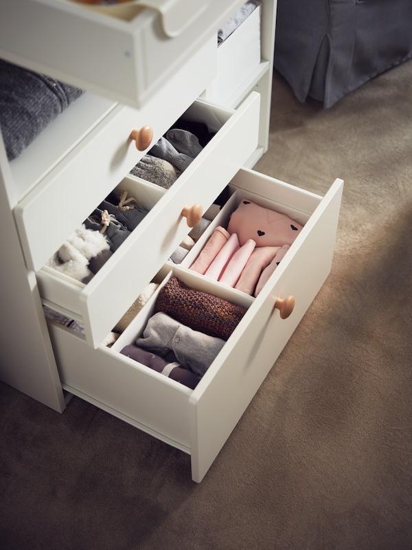 Des boîtes compartimentées RASSLA blanches contiennent des vêtements de bébé dans des tiroirs blancs sur un tapis brun.