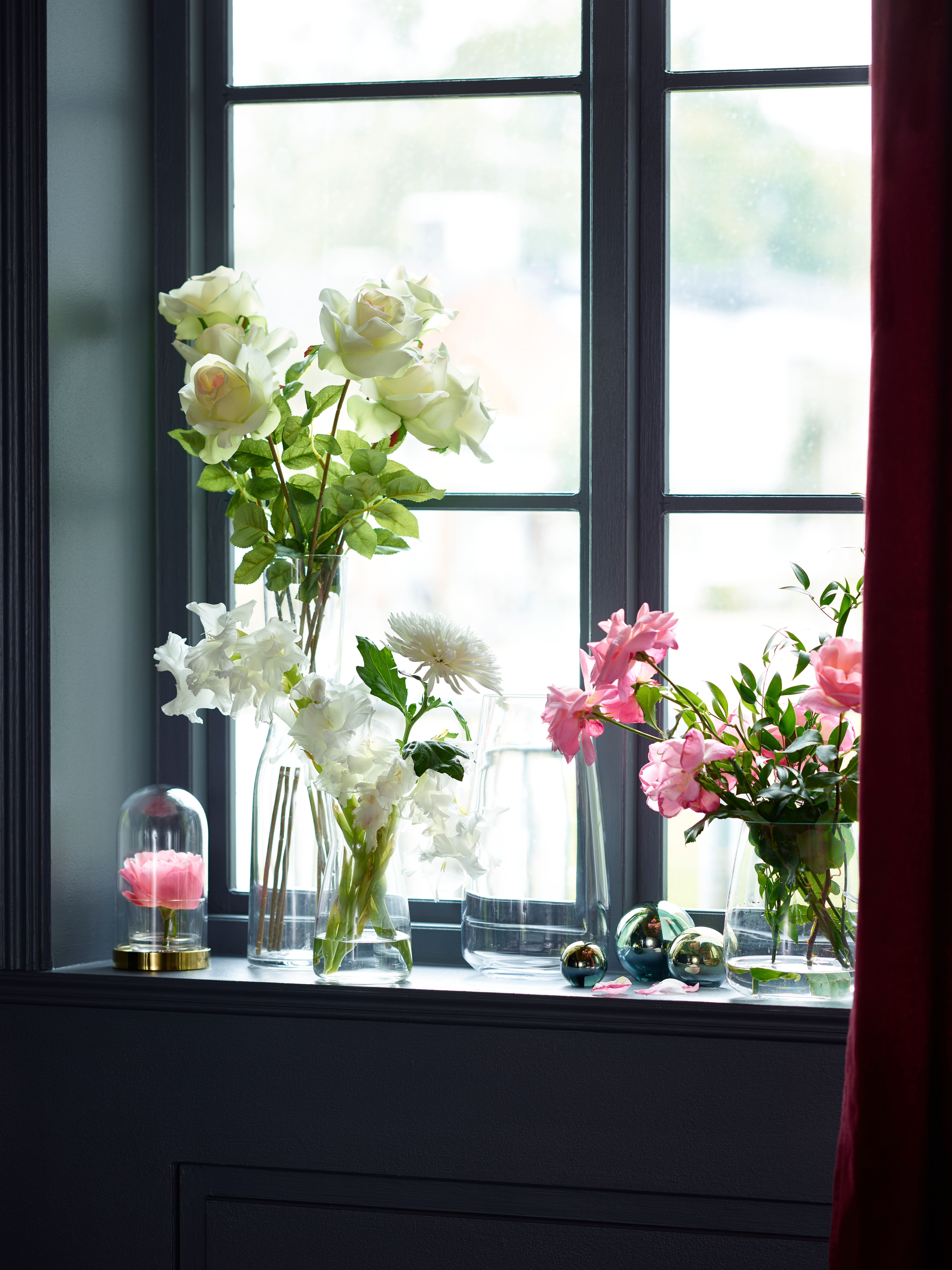 Several clear glass BERÄKNA vases hold pink and white flowers. They sit on a deep windowsill near a light-filled window.