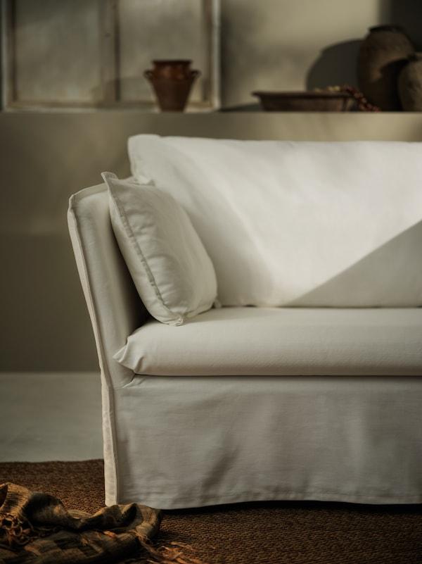 Valkoinen BACKSÄLEN 1,5-paikkainen nojatuoli seisoo olohuoneessa maanläheisellä matolla. Huopa on lähellä lattiaa.
