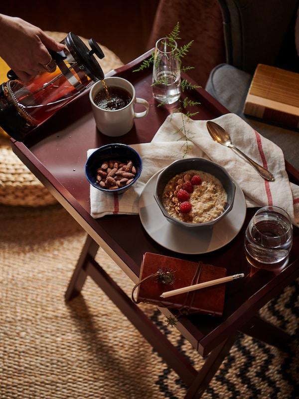 Ein dunkelroter Tabletttisch. Auf ihm sind eine Schüssel Porridge mit Himbeeren, eine Schüssel Nüsse und eine Tasse Kaffee zu sehen.