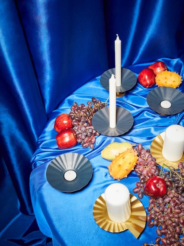 KARISMATISK Kerzen- oder Teelichthalter aus Metall in Blau/Goldfarben und goldfarbene Kerzenschalen stehen auf einem Tisch, der mit einem blauen Satinstoff bedeckt ist.