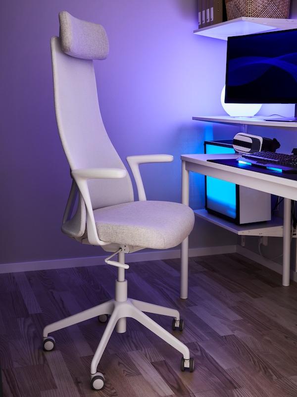 パソコン、パソコンモニター、ブルーの光のランプを設置したテーブルと棚の隣に、ベージュ/ホワイトのオフィスチェアが置かれている。