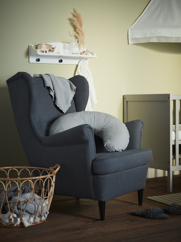 En hvid væghylde, en lænestol, en grå ammepude, en grå, strikket babyplaid, en grå tremmeseng og en hvid sengehimmel.