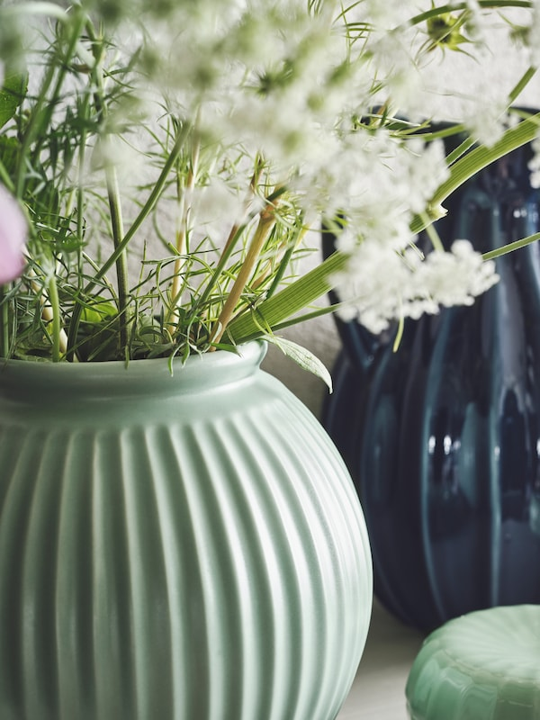 A large green vase with plant cuttings of various types, some with white blooms, in front of another vase in dark blue.