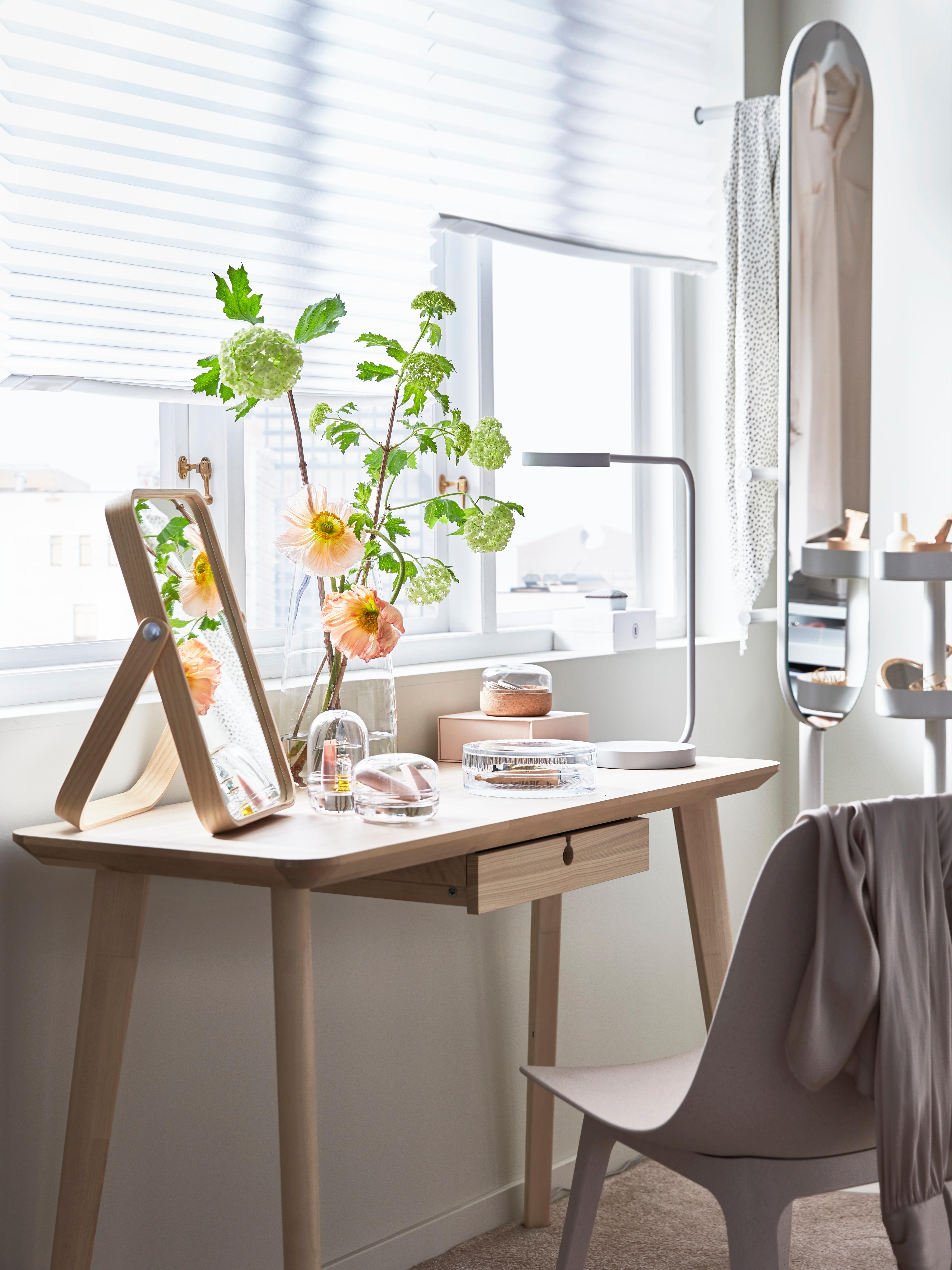 Radni sto LISABO s pepeljastim furnirom, s cvećem u vazi, ogledalom i lampom, ispred prozora s belim roletnama.