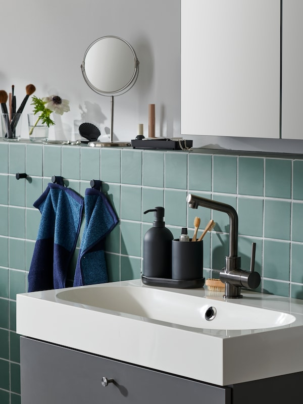 Et GANSJÖN badeværelsessæt står på en vask omgivet af gæstehåndklæder, et spejl og tilbehør på en muret hylde.