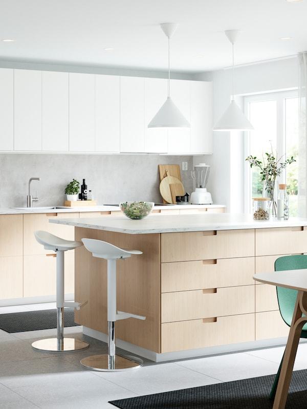 Cucina con ante e frontali cassetti in bianco/bambù, isola per cucina, due sgabelli bar, due lampade a sospensione e sedie verdi.