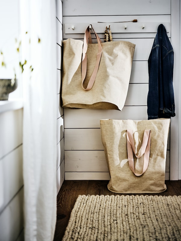 A white wood panelled wall with a row of hooks holding a large beige bag and a coat. A beige bag is below on the floor.